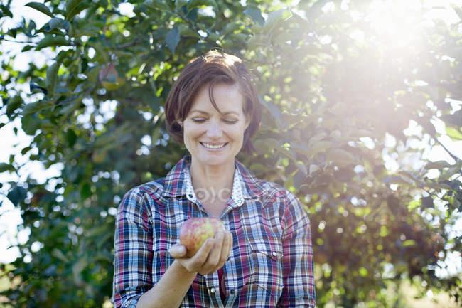 Woman holding fresh picked apple — Stock Photo