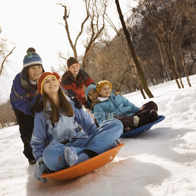 Children riding on sledges on the snow. — Stock Photo