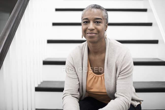 Зрелая женщина, сидящая на лестнице — стоковое фото