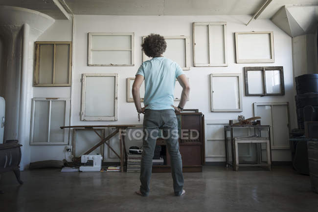 Человек с руками на бедрах, глядя на стену — стоковое фото