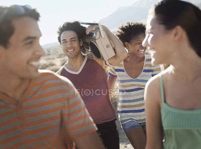 People walking on the open road with a boombox. — Stock Photo