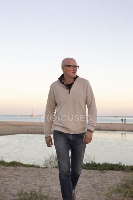 Mann mit Glatze läuft an einem Sandstrand — Stockfoto