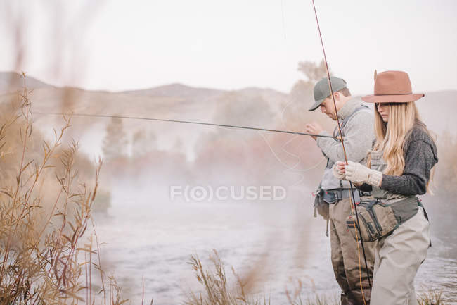 Couple fishing on a riverbank — Stock Photo