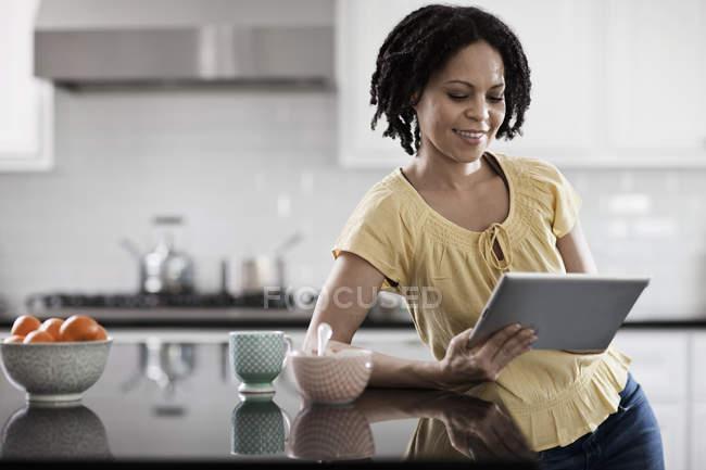 Жінка в домашніх умовах використовуючи цифровий планшетний. — стокове фото