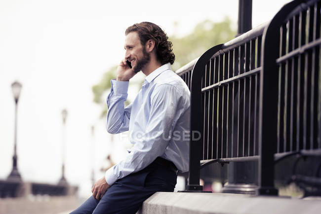 Man seated on a step making a call — Stock Photo