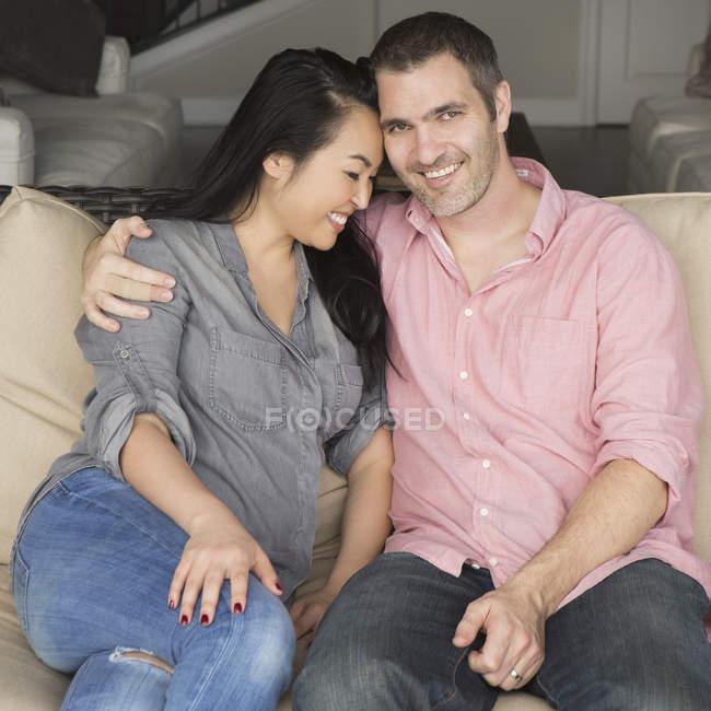 Lächelnder Mann und Frau auf einem Sofa — Stockfoto