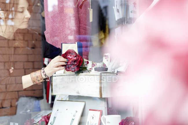 Woman rearranging window display — Stock Photo