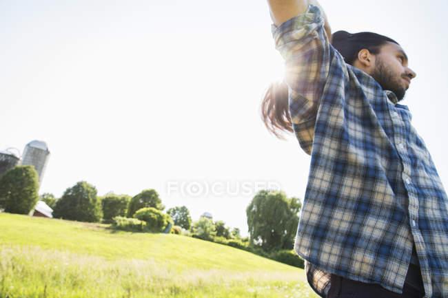 Молода людина, піднімаючи руки в області — стокове фото