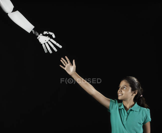 Girl reaching up to robotic hand. — Stock Photo