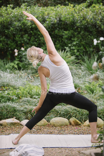 Woman doing yoga in a garden. — Stock Photo