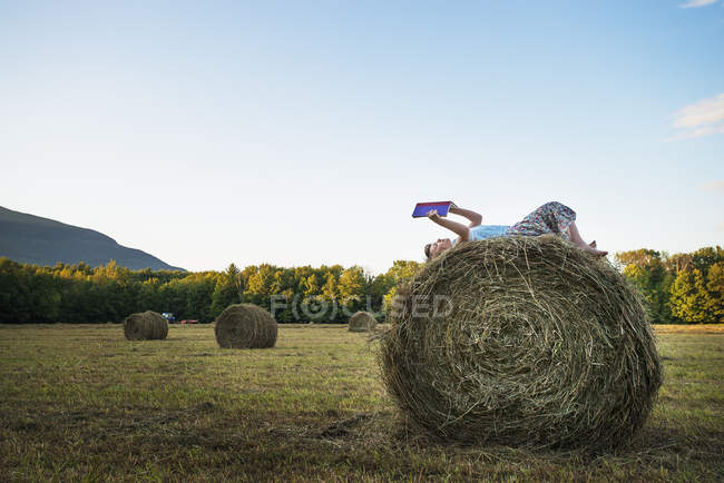 Girl sitting on the top of bale. — Stock Photo