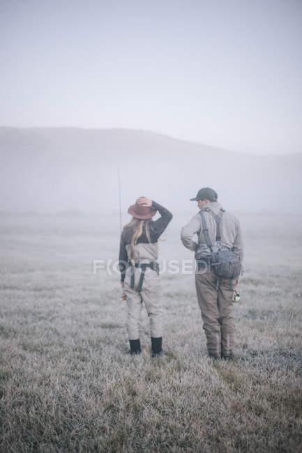 Pareja caminando en la niebla de la mañana - foto de stock