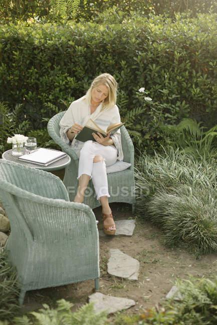 Жінка, сидячи в саду, читання. — стокове фото