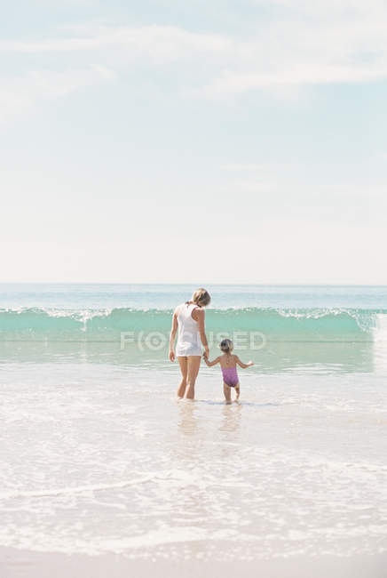 Woman with daughter watching a wave. — Stock Photo