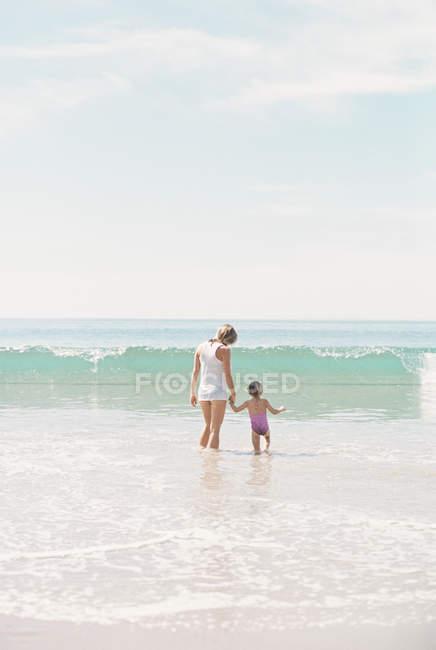 Женщина с дочерью наблюдает за волной . — стоковое фото