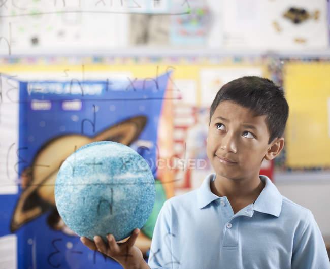 Junge hält einen Globus — Stockfoto