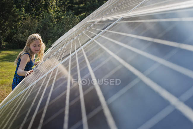 Young girl beside solar panel — Stock Photo
