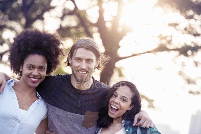 Man and two women side by side smiling — Stock Photo