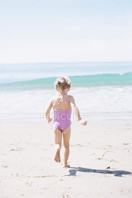 Young girl in a pink swimsuit running — Stock Photo
