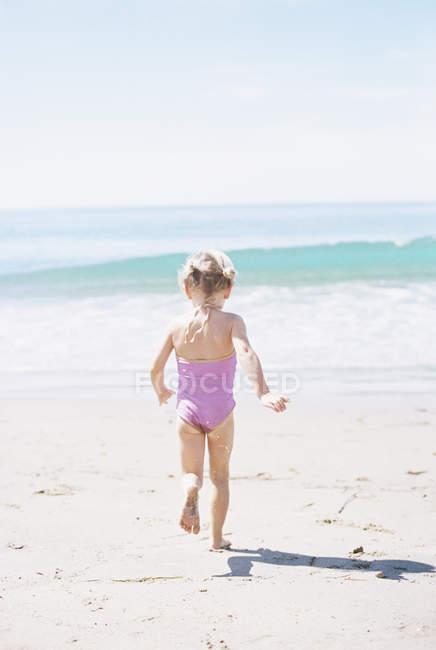 Junges Mädchen im rosa Badeanzug läuft — Stockfoto