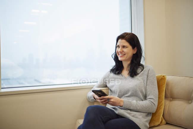 Donna d'affari seduta vicino a una finestra — Foto stock