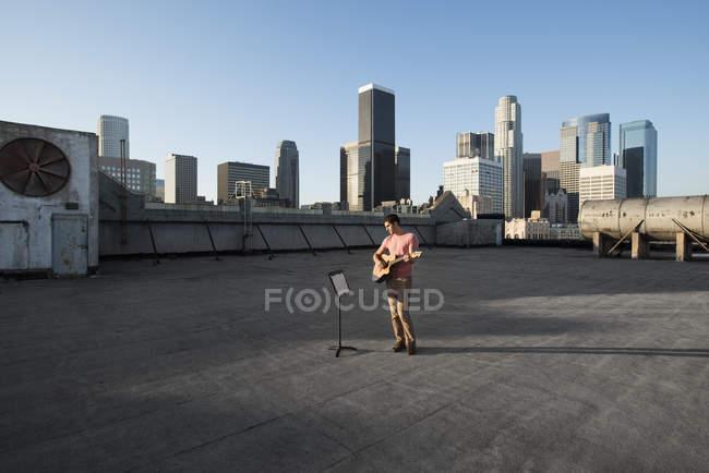 Человек играет на гитаре на крыше — стоковое фото