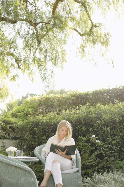Woman sitting in a garden, reading — Stock Photo