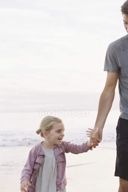 Homme jouant sur une plage de sable avec fille — Photo de stock