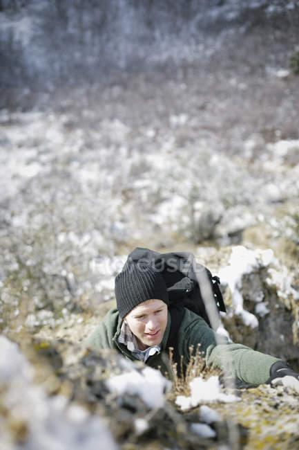 Uomo che si arrampica su una parete di roccia ripida. — Foto stock