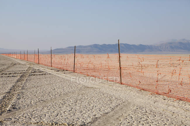 Fence extending across the flat landscape — Stock Photo