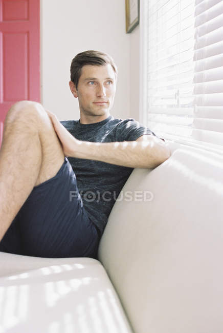 Man sitting on a sofa by a window — Stock Photo