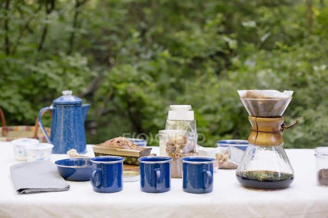 Tabelle in einem Garten, mit einer Kaffeemaschine — Stockfoto