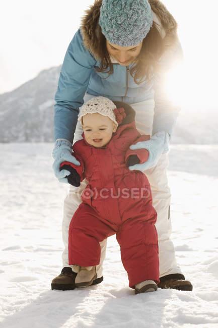 Mère et bébé dehors dans la neige — Photo de stock