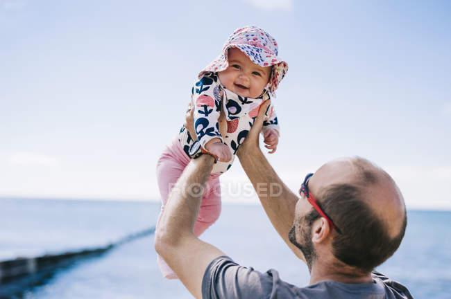 Батько, піднімаючи його немовляти дочки — стокове фото