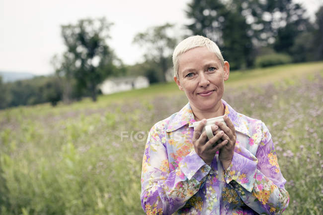 Woman with hands wrapped around a coffee cup — Stock Photo