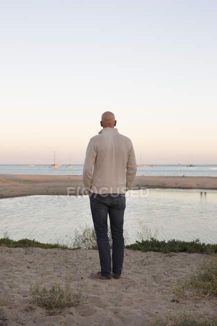 Homem careca em pé em uma praia de areia — Fotografia de Stock