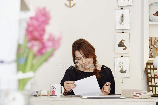 Woman sitting at desk doing paperwork — Stock Photo