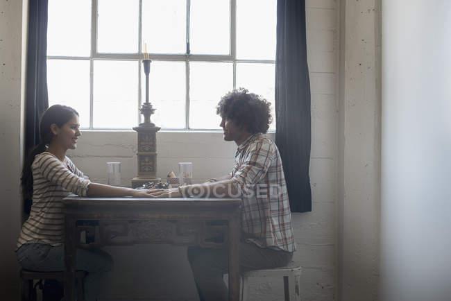 Пара, взявшись за руки через стол — стоковое фото