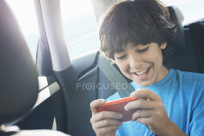 Boy playing games on smart phone — Stock Photo