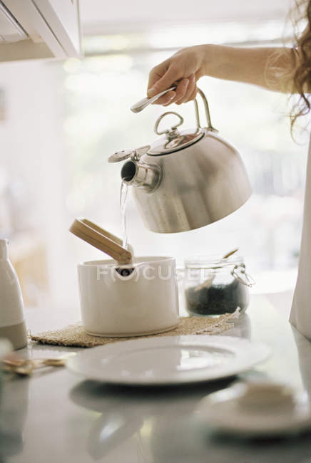 Pouring hot water into a tea pot. — Stock Photo
