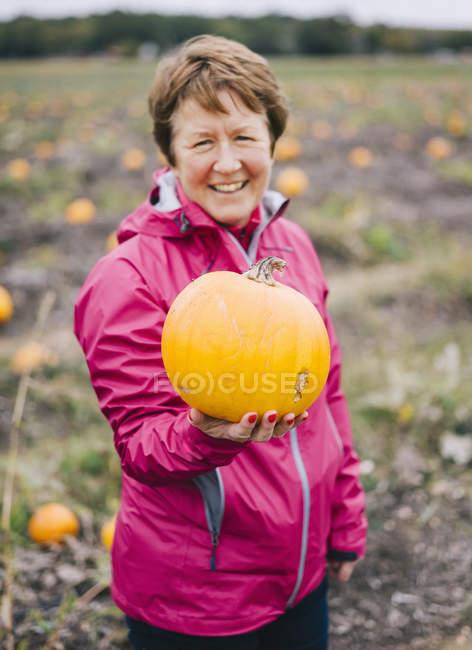 Mature woman holding orange pumpkin. — Stock Photo
