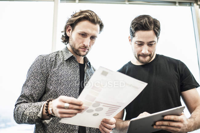 Two men standing in an office — Stock Photo