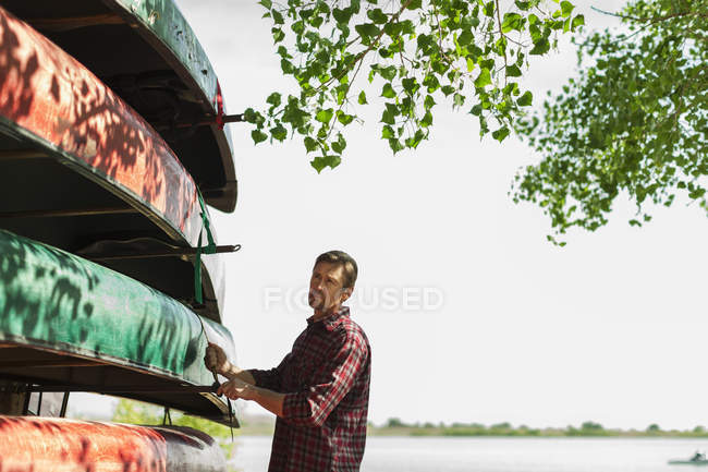 Man stacking narrow rowing boats — Stock Photo