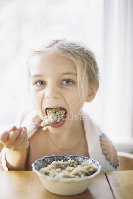 Menina tomando café da manhã de uma tigela . — Fotografia de Stock