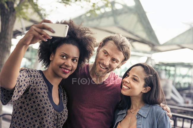 Homme et deux femmes, prendre des selfies dans le parc — Photo de stock