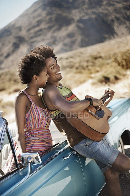 Couple standing by a pale blue convertible — Stock Photo