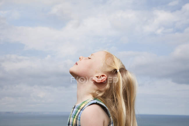 Young girl raising her face — Stock Photo