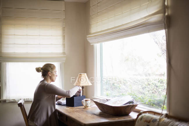Woman sitting at a desk by a window — Stock Photo