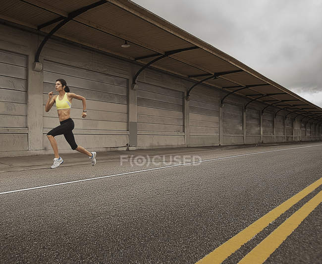 Женщина бежит по городской дороге — стоковое фото