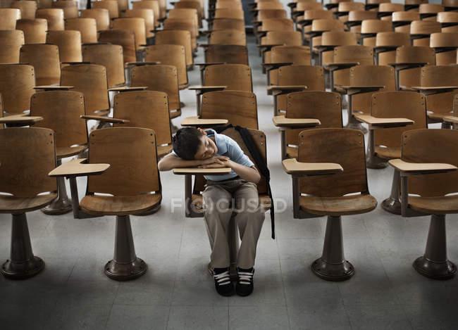 Мальчик в зале пустых парт — стоковое фото